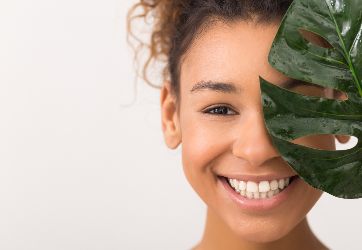 Woman with beautiful skin behind leaf for top clear skin tips