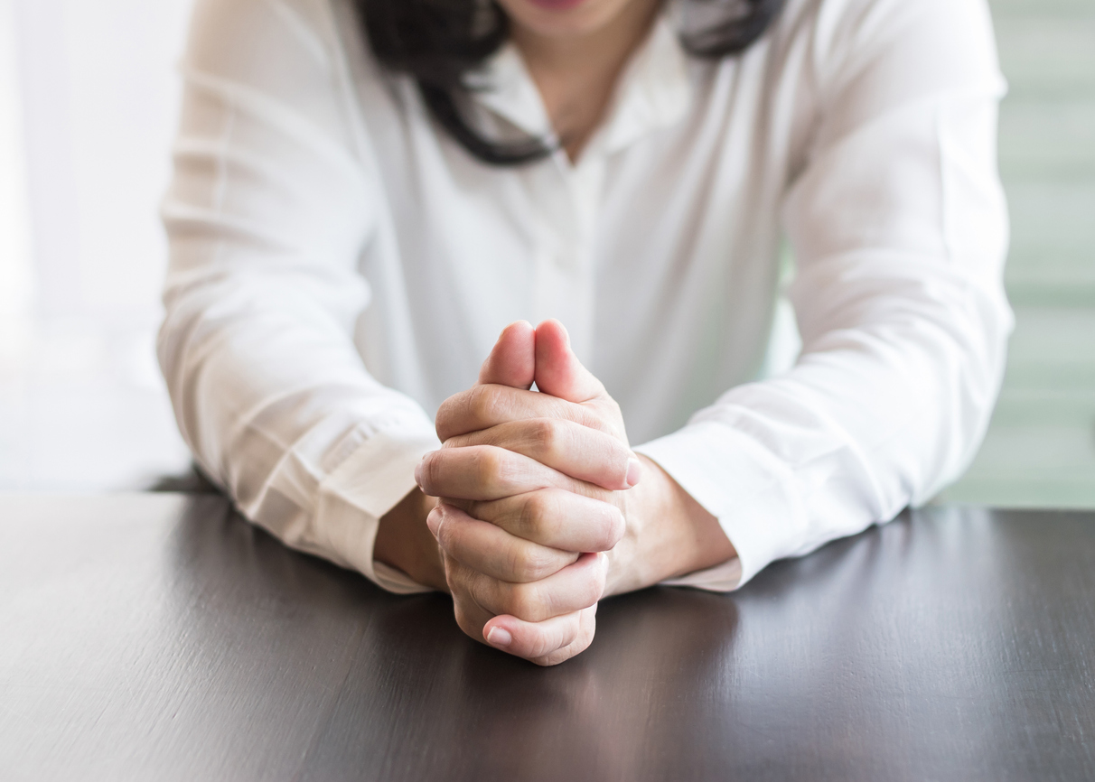 Woman self-conscious clasping sweaty hands