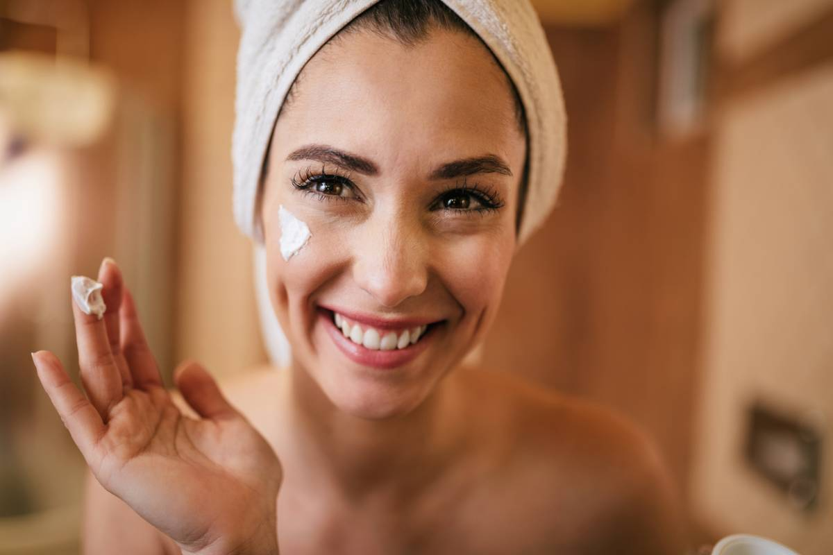 woman smiling with towel wrapping her hair